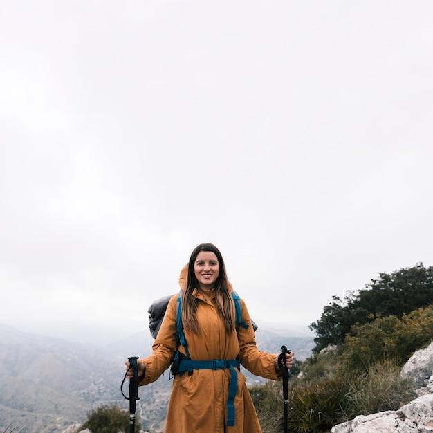 Porträt einer lächelnden jungen frau, die auf die oberseite des berges hält wanderstock steht Kostenlose Fotos