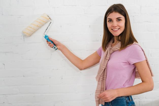 Porträt einer lächelnden jungen frau, die die lackrolle auf weißer backsteinmauer verwendet Kostenlose Fotos