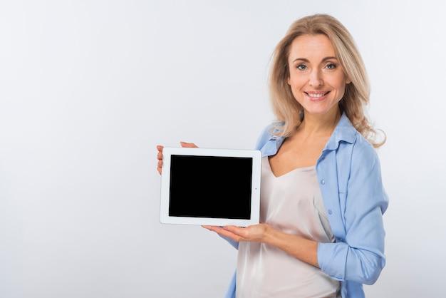 Porträt einer lächelnden jungen frau, die digitale tablette gegen weißen hintergrund zeigt Kostenlose Fotos