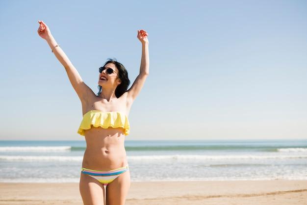 Porträt einer lächelnden jungen frau im bikini, der nahe dem meer gegen blauen himmel am strand steht Kostenlose Fotos