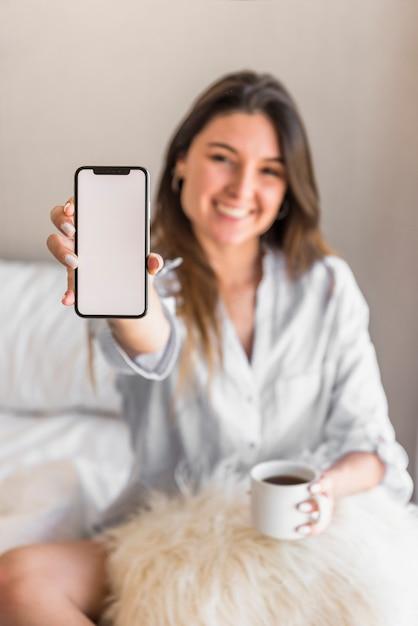 Porträt einer lächelnden jungen frau, welche die kaffeetasse zeigt intelligenten telefonschirm hält Kostenlose Fotos