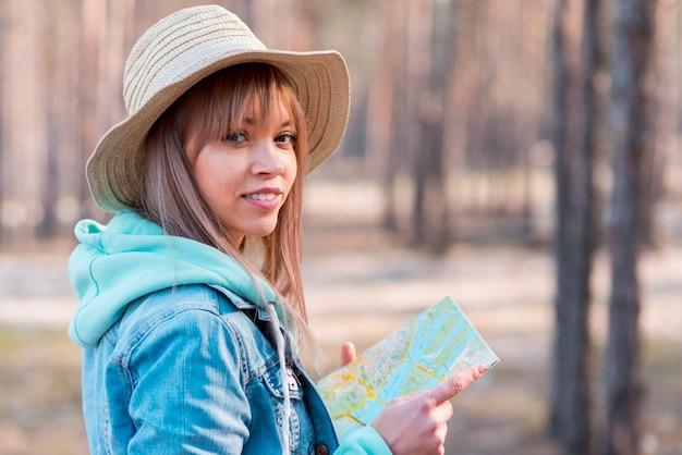 Porträt einer lächelnden jungen frau, welche die karte in der hand betrachtet kamera hält Kostenlose Fotos