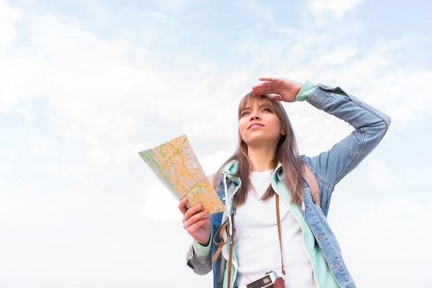 Porträt einer lächelnden jungen frau, welche die karte in der hand schützt ihre augen gegen himmel hält Kostenlose Fotos