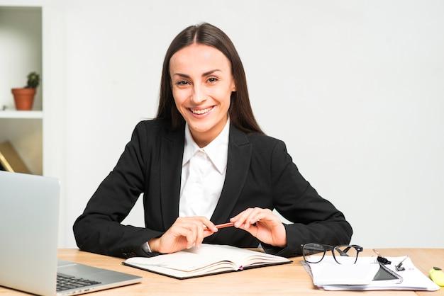 Porträt einer lächelnden jungen geschäftsfrau, die am schreibtisch mit bleistift und tagebuch sitzt Kostenlose Fotos
