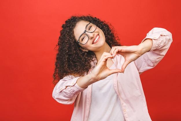 Porträt einer lächelnden jungen lockigen frau, die herzgeste mit zwei händen zeigt und kamera lokalisiert über rotem hintergrund betrachtet. Premium Fotos