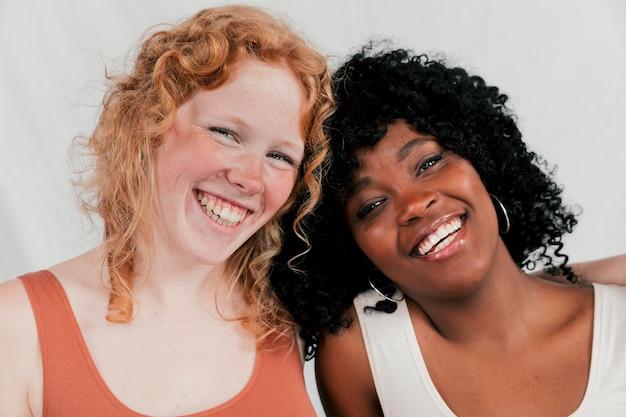 Porträt einer lächelnden jungen multi ethnischen freundin, die kamera betrachtet Kostenlose Fotos