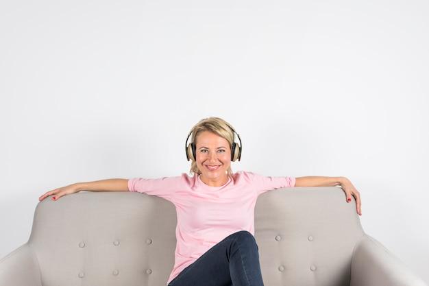 Porträt einer lächelnden reifen frau, die auf dem sofa betrachtet kamera gegen weißen hintergrund sitzt Kostenlose Fotos