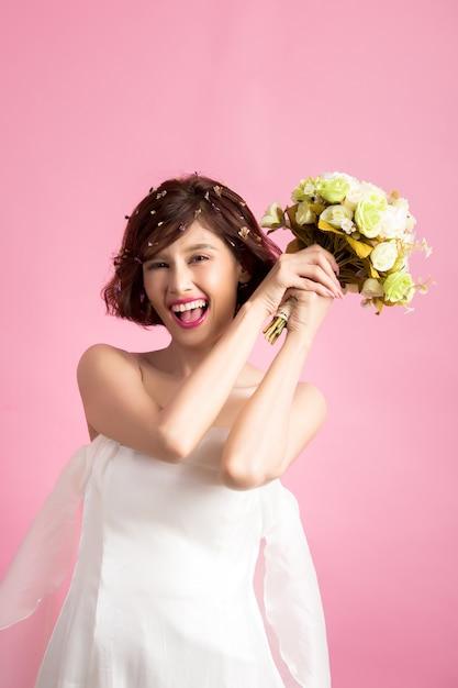 Porträt einer lächelnden spielerischen netten frau, die blumen lokalisiert auf rosa hält Kostenlose Fotos