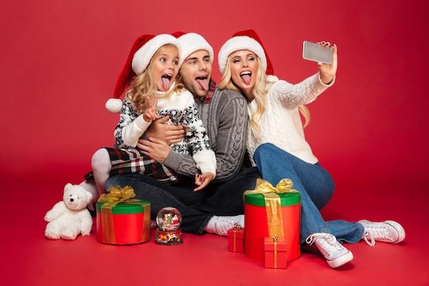 Porträt einer lustigen familie mit einem kind in voller länge Kostenlose Fotos