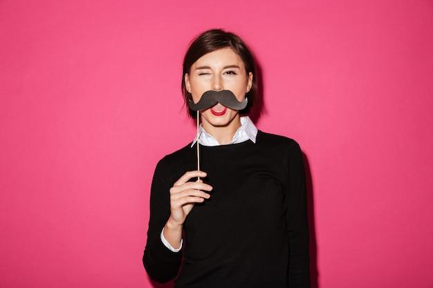Porträt einer lustigen jungen geschäftsfrau mit dem papierschnurrbart Kostenlose Fotos