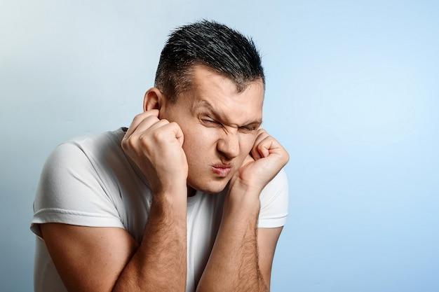 Porträt einer mannnahaufnahme des verstemmens von ohren, die den ton blockieren würden Premium Fotos