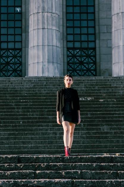 Porträt einer modernen jungen frau, die auf dem treppenhaus betrachtet kamera steht Kostenlose Fotos