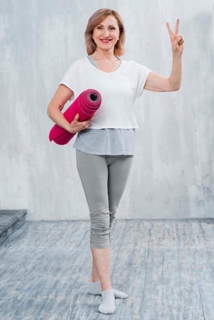 Porträt einer schönen alten frau mit der yogamatte, die zu hause siegeszeichen zeigt Kostenlose Fotos