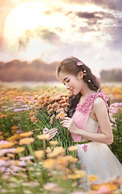 Porträt einer schönen asiatischen frau in einem blumenfeld Premium Fotos
