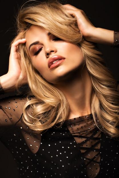 Porträt einer schönen blondine auf einem schwarzen Premium Fotos