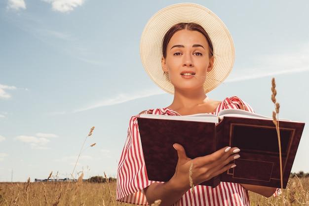 Porträt einer schönen dame. liest ein buch auf dem feld. bereite dich auf den hochschulzugang vor. Kostenlose Fotos