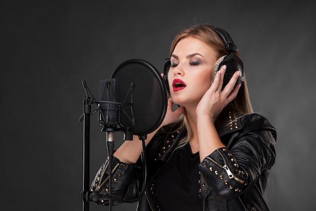 Porträt einer schönen frau, die mit kopfhörern ins mikrofon singt Kostenlose Fotos