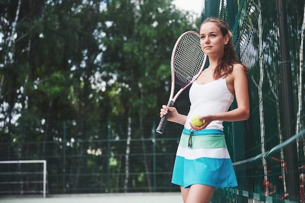 Porträt einer schönen frau, die tennis übt. Kostenlose Fotos