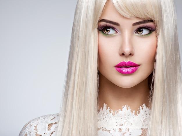 Porträt einer schönen frau mit langen weißen glatten haaren und hellem make-up. gesicht eines mode-modells mit rosa lippenstift. hübsches mädchen posiert. Kostenlose Fotos