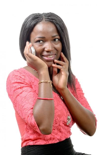 Porträt einer schönen jungen afrikanischen frau, die am handy gegen weiß spricht Premium Fotos