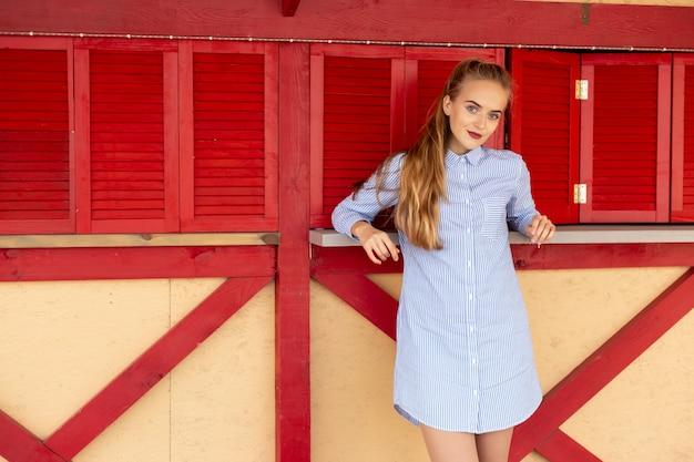 Porträt einer schönen jungen frau auf dem hintergrund einer roten hölzernen wand Premium Fotos