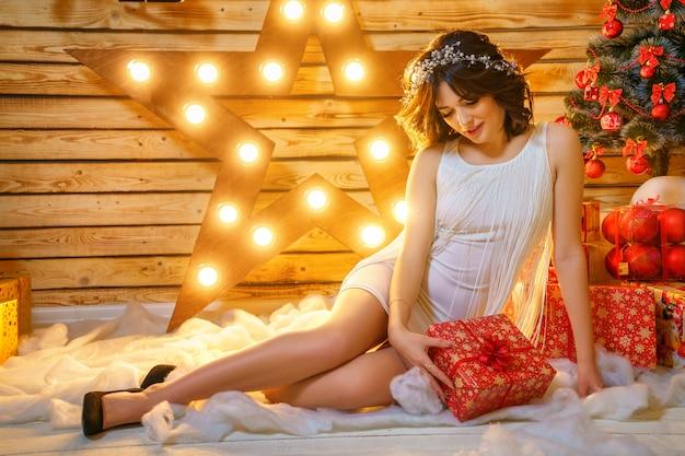 Porträt einer schönen jungen frau auf dem hintergrund eines weihnachtsbaums Premium Fotos