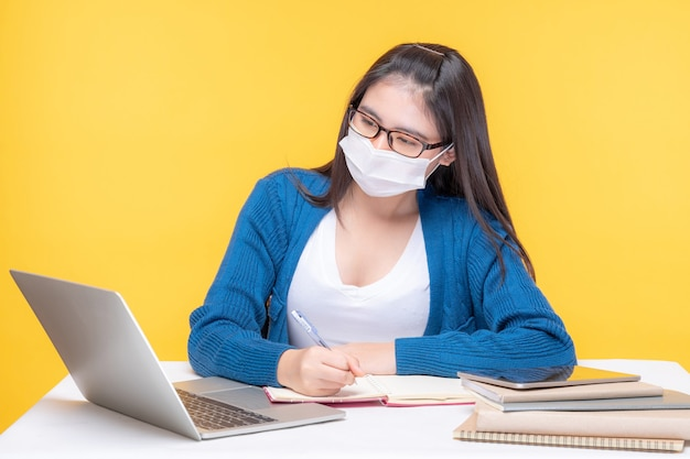 Porträt einer schönen jungen frau, die am tisch mit laptop und notizbuch zu hause studiert - online-e-learning-system studierend Kostenlose Fotos