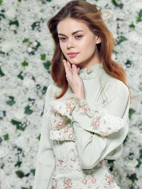 Porträt einer schönen jungen frau hintergrund der blumen in einem blumenkleid Premium Fotos