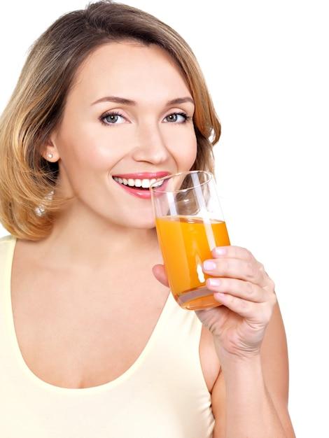 Porträt einer schönen jungen frau mit einem glas orangensaft lokalisiert auf weiß. Kostenlose Fotos