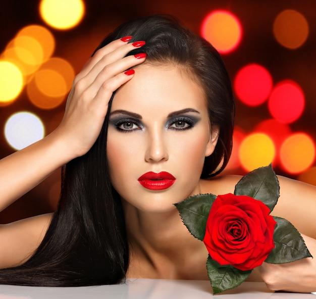 Porträt einer schönen jungen frau mit roten lippen, nägeln und rosenblume in der hand. modemodell mit dem make-up des blauen auges, das im studio über nachtlichtkugeln aufwirft. weiches bokeh-hintergrundkonzept. Kostenlose Fotos
