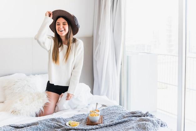 Porträt einer schönen lächelnden jungen frau auf bett mit frühstück Kostenlose Fotos