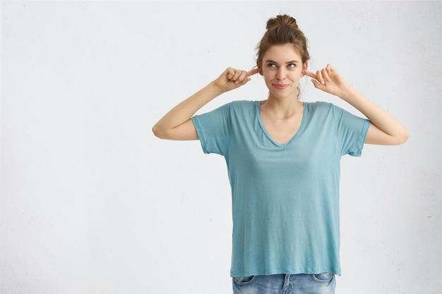 Porträt einer schönen lässig gekleideten jungen frau, die vorgibt, nicht zu hören, was ihr gesagt wird Kostenlose Fotos