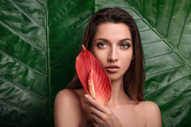 Porträt einer schönen tropischen brünette mit einer roten anthuriumblume in ihren händen. Premium Fotos