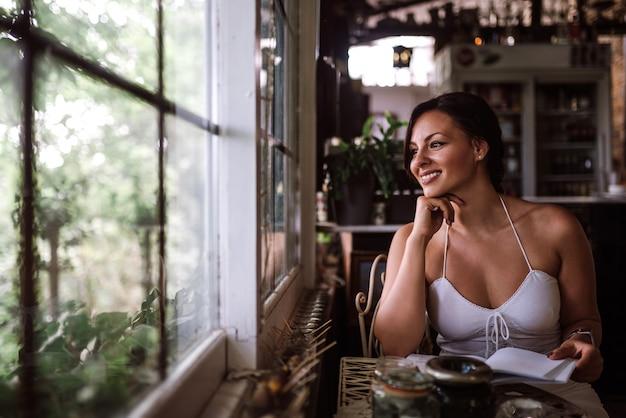 Porträt einer schönheit, die durch fenster beim sitzen im wintergarten oder im wintergarten schaut. Premium Fotos