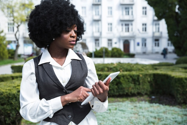 Porträt einer überzeugten afrikanischen jungen geschäftsfrau, die digitale tablette betrachtet Kostenlose Fotos