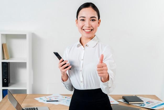 Porträt einer überzeugten jungen geschäftsfrau, die daumen herauf zeichen in richtung zur kamera im büro zeigt Kostenlose Fotos