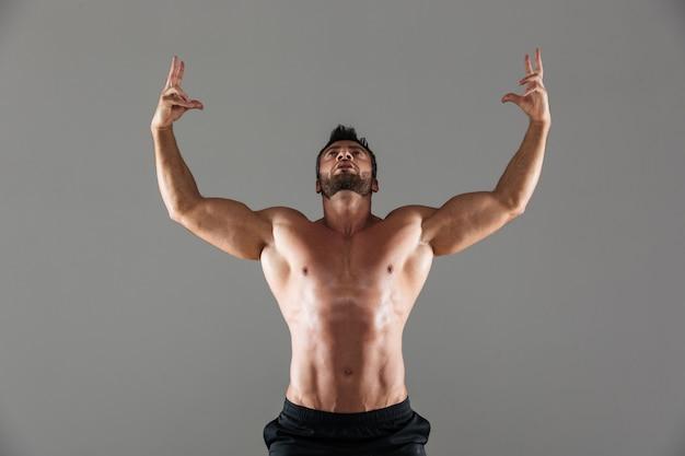 Porträt einer überzeugten starken hemdlosen männlichen bodybuilderaufstellung Kostenlose Fotos