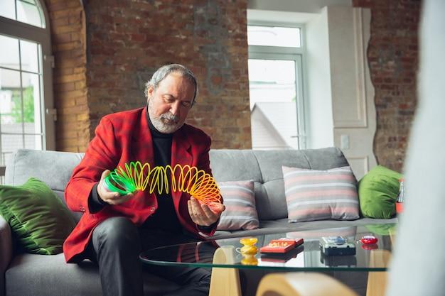 Porträt eines älteren mannes mit retro-dingen, spielzeug, begegnung mit dingen aus der vergangenheit Kostenlose Fotos