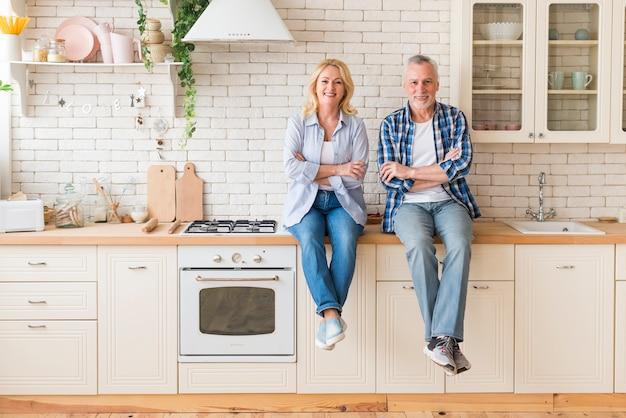 Porträt eines älteren paares mit ihren armen kreuzte das sitzen auf küchenarbeitsplatte Kostenlose Fotos
