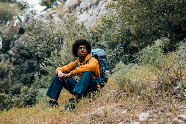 Porträt eines afrikanischen männlichen wanderers, der das stillstehen im berg sitzt Kostenlose Fotos