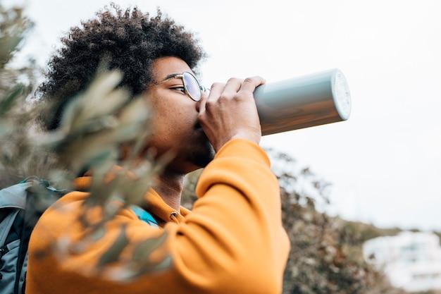 Porträt eines afrikanischen mannes, der das wasser trinkt Kostenlose Fotos