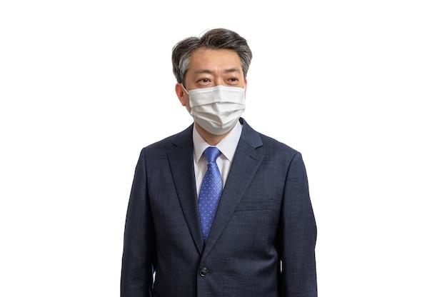 Porträt eines asiatischen geschäftsmannes mittleren alters, der eine weiße gesichtsmaske trägt. Premium Fotos