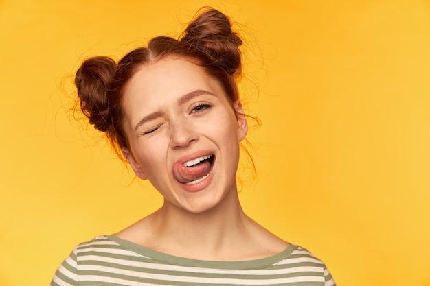 Porträt eines attraktiven mädchens mit roten haaren und zwei brötchen. habe eine spielerische, dumme stimmung. tragen sie einen gestreiften pullover, zwinkern sie und zeigen sie eine zunge isoliert, nahaufnahme über gelber wand Kostenlose Fotos