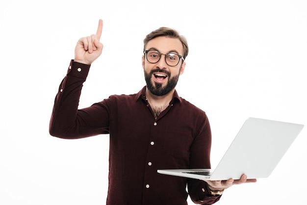 Porträt eines aufgeregten bärtigen mannes, der laptop-computer hält Kostenlose Fotos