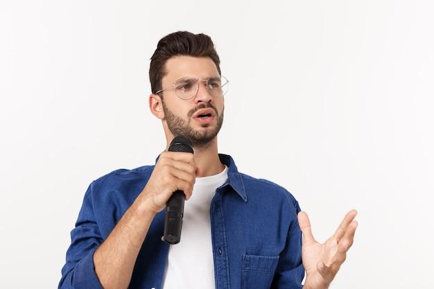 Porträt eines aufgeregten jungen mannes im t-shirt lokalisiert über dem grauen backgound, singend. Premium Fotos