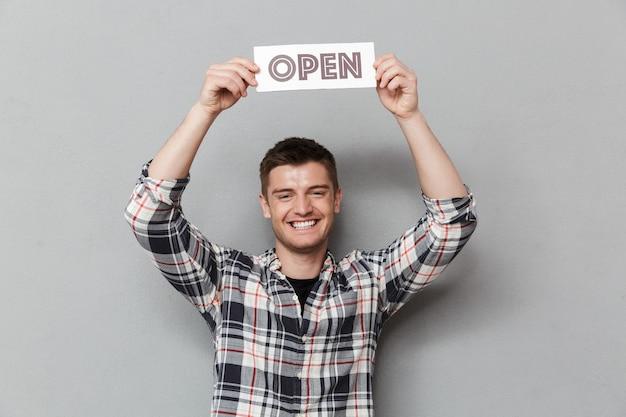 Porträt eines aufgeregten jungen mannes mit offenem zeichen Premium Fotos