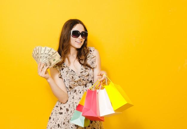 Porträt eines aufgeregten schönen mädchens mit der sonnenbrille, die einkaufstaschen lokalisiert über gelb hält Premium Fotos