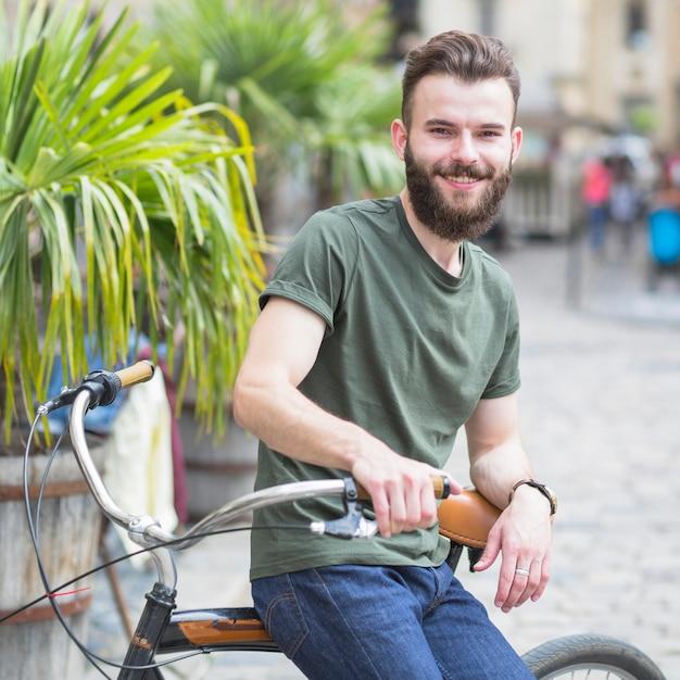 Porträt eines bärtigen jungen männlichen radfahrers, der auf fahrrad sitzt Kostenlose Fotos