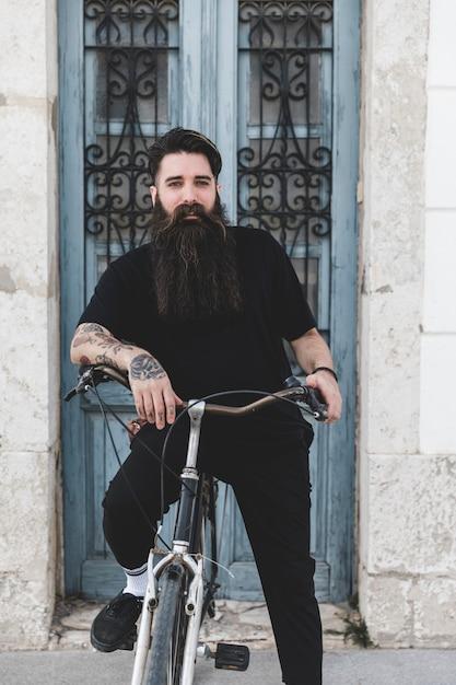 Porträt eines bärtigen jungen mannes mit seinem fahrrad Kostenlose Fotos