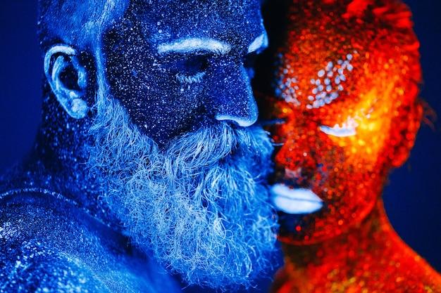 Porträt eines bärtigen mannes und der frau gemalt im uv-pulver. Premium Fotos